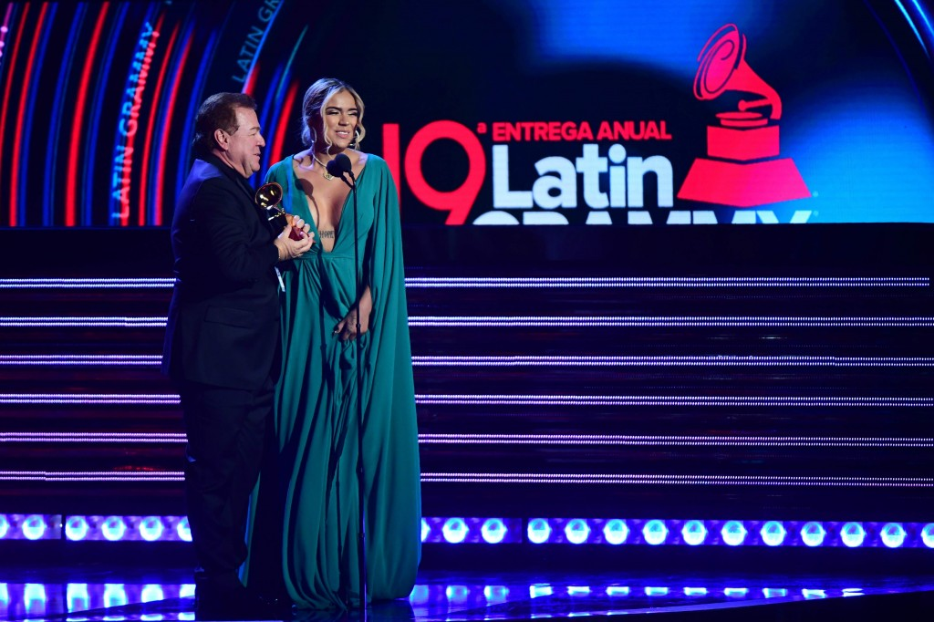 Karol G ganó su primer Grammy Latino en la categoría de Mejor Nuevo Artista. Lo subió a recibir con su padre. FOTO AFP