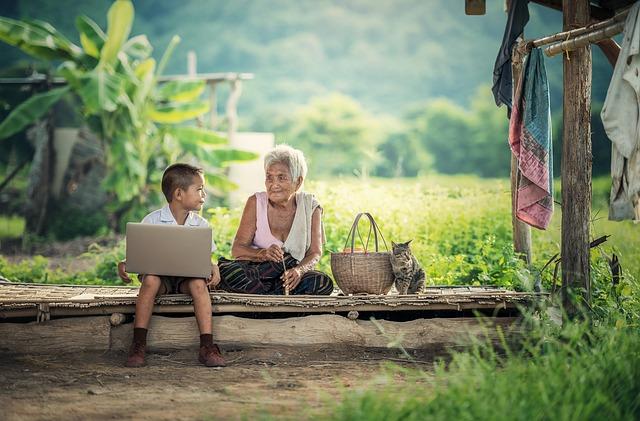 niño con computador y abuela en el campo