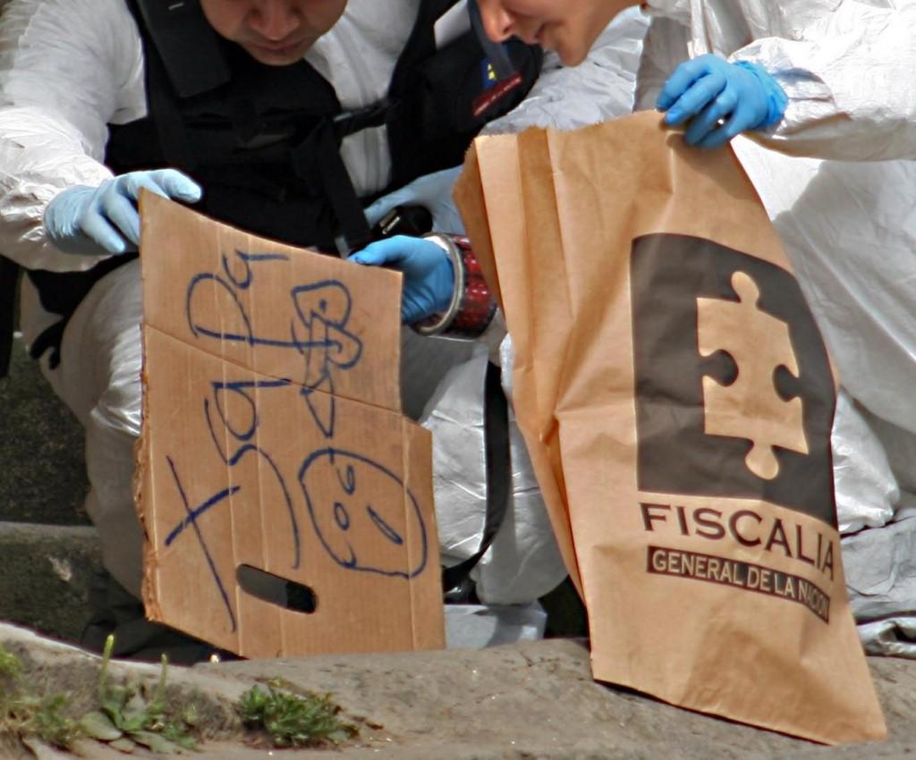 Esta imagen corresponde a un homicidio del 16 de junio de 2011, cuando una despachadora de buses fue asesinada a bala en una calle de la comuna 13. Los agresores dejaron ese mensaje en un pedazo de cartón, junto a la víctima. FOTO: Carlos Taborda (Archivo).