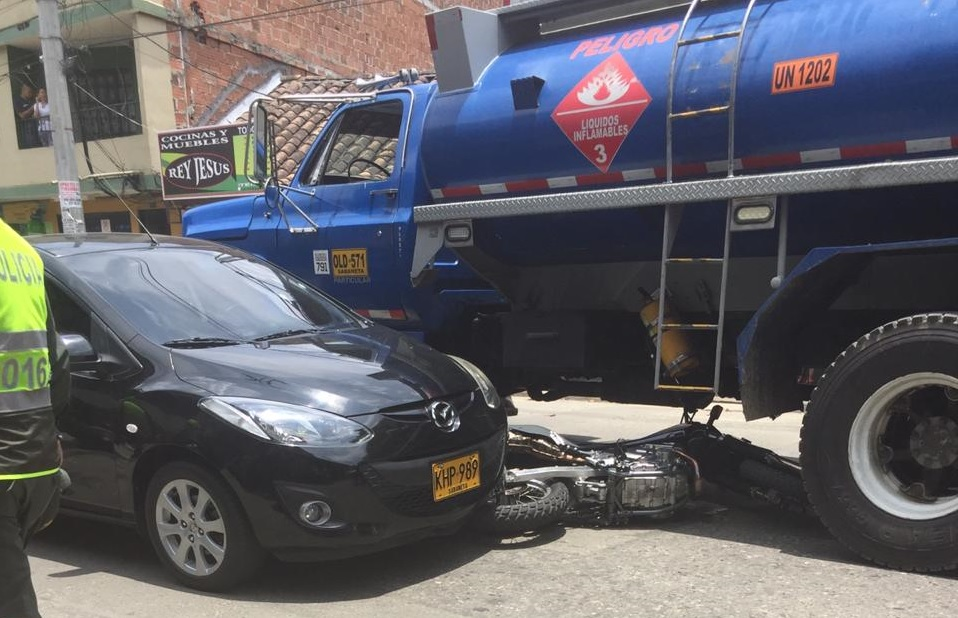 En este automóvil se transportaban los tres miembros de la familia, cuando los atacaron en la frontera de los barrios El Mesa y El Cairo, en Bello. Al lado quedó la moto de los sicarios. Foto cortesía de Guardianes Antioquia.